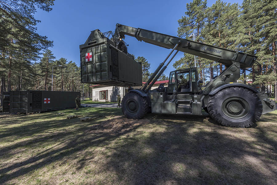 Canadian troops use an RT240 rough terrain container handler to move medical pods in advance of the arrival of NATO's enhanced Forward Presence multinational battlegroup at Camp Ādaži, Latvia, during Operation REASSURANCE on May 21, 2017.
