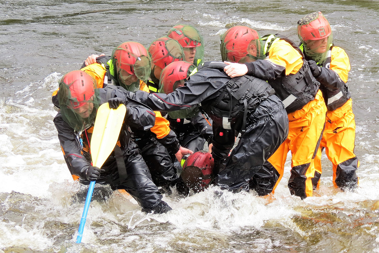 Soldiers work as a team to carry a simulated rescued victim to the river bank during swift water rescue training on the Shadow River near Parry Sound, Ontario on May 26, 2017.