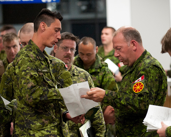 Traffic technicians inspect soldiers' documentation at Edmonton International Airport prior to boarding a military aircraft to deploy on Operation REASSURRANCE on June 9th, 2017. Photo: Robert Schwartz, 3rd Canadian Division Support Base. ©2017 DND-MDN Canada