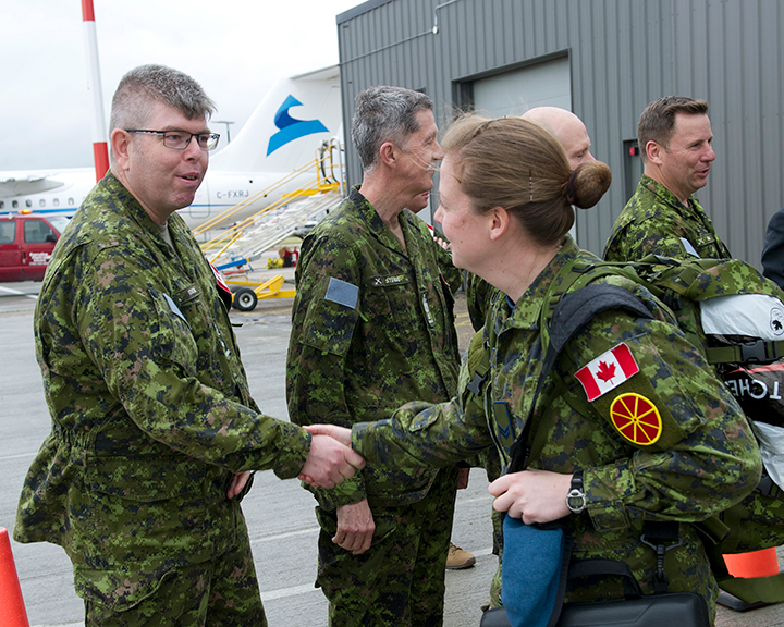 Brigadier-General Nic Stanton, Acting Commander of 3rd Canadian Division, shakes the hand of a soldier deploying on Operation REASSURANCE from Edmonton International Airport on June 9, 2017.