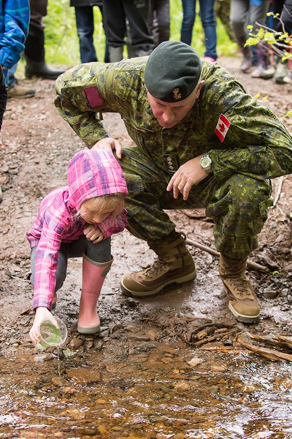 Commander Colonel Keith Osmond and a student from a local school release baby salmon into the brook at the 10th annual Fish Friends Field Day at the 5th Canadian Division Support Group Gagetown, in Oromocto, New Brunswick on June 6, 2017. 
