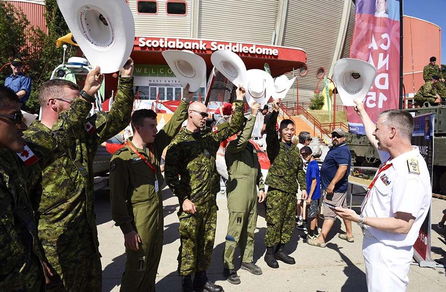 A group of military members wave their white cowboy hats at the Calgary Stampede in support of the military display set up on the Calgary Stampede grounds from July 7 to 16, 2017.