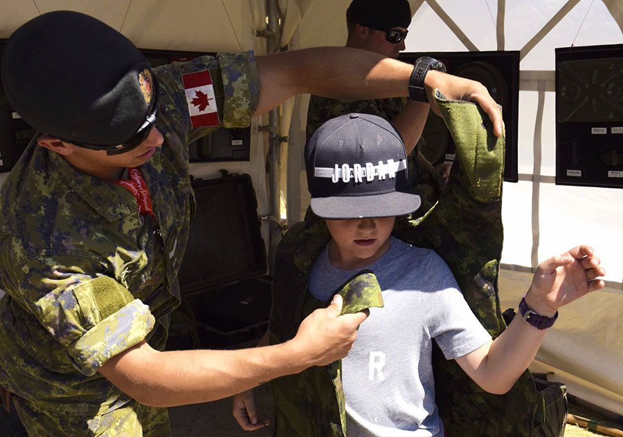 Corporal Tyler Graves of 41 Combat Engineer Regiment, shows a young visitor how to don a flak vest at the military display set up on the Calgary Stampede grounds from July 7 to 16, 2017.