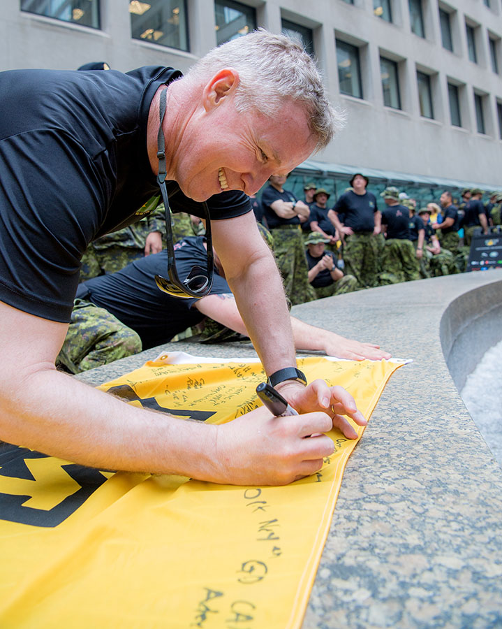 Brigadier General Steven Cadden, Commander of the 4th Canadian Division, signs the Invictus Games flag after it was carried through the streets of downtown Toronto by Canadian Forces members during the 100-day Invictus Games countdown on June 15, 2017.