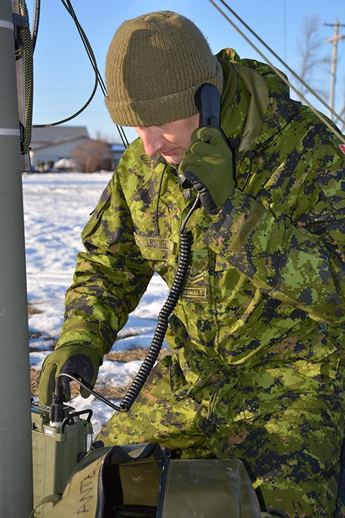 Master Corporal James Kletchko, of 38 Signal Regiment, tests the equipment at Land Task Force Headquarters during Exercise ARCTIC BISON held at Gimli, Manitoba from February 18 to 25, 2017.