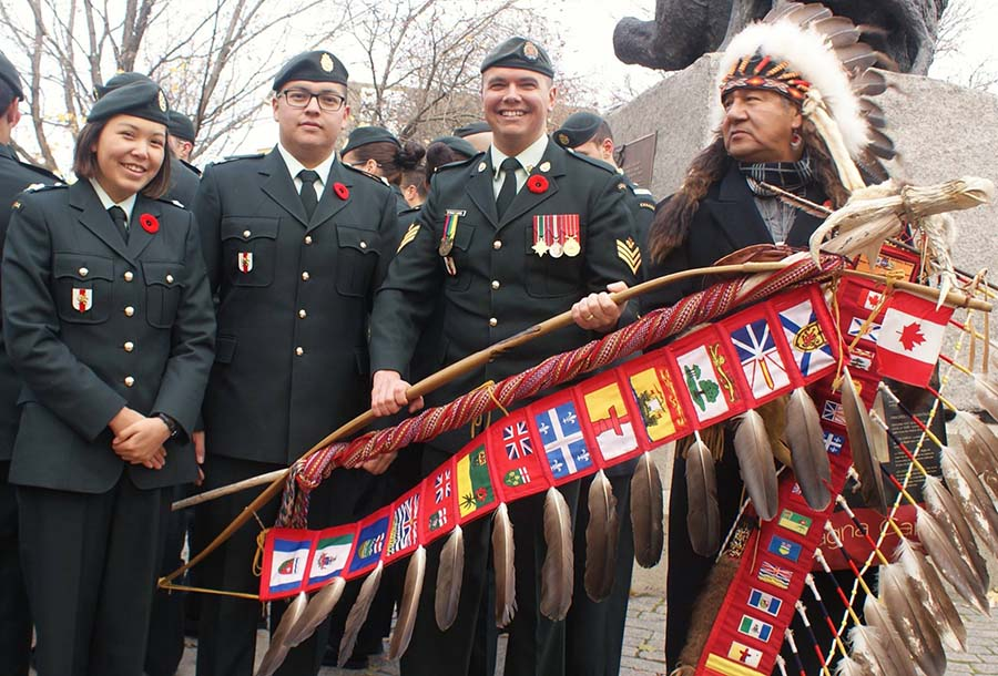 Sergeant Moogly Tetrault-Hamel, the Indigenous Advisor to the Chaplain General of the Canadian Armed Forces, holds the Canadian Armed Forces/Department of National Defence Eagle Staff on Remembrance Day in 2016 at the National Aboriginal Veterans Monument in Ottawa, Ontario. Sergeant Tetrault-Hamel is joined by two Royal Military College of Canada officer cadets and Ojibway Elder Bernard Nelson.  Photo: ©2017 DND/MDN Canada.