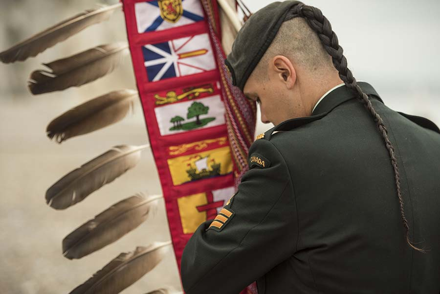 Soldier carries the Canadian Armed Forces/Department of National Defence Eagle Staff