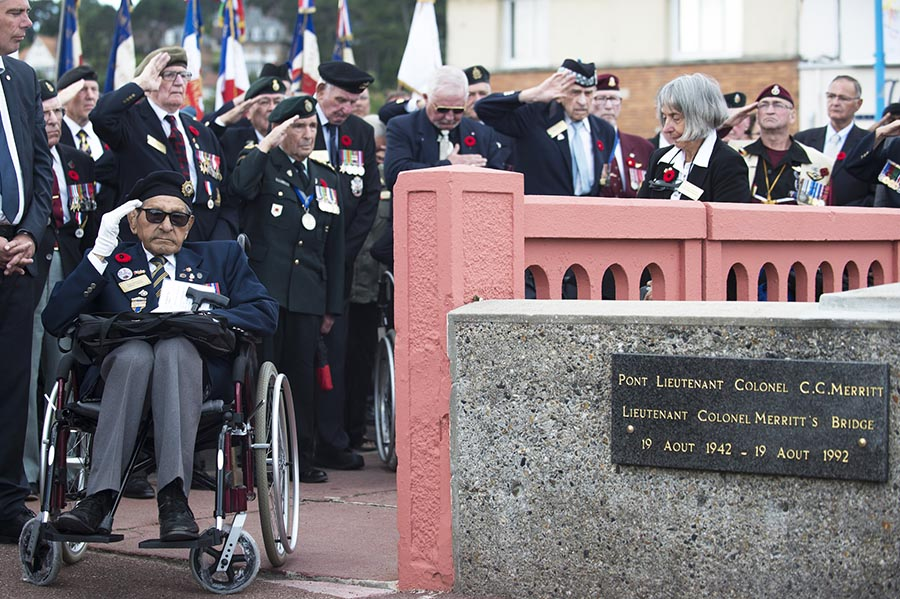 Paul Delmore (left), and Honorary Colonel David Lloyd Hart (centre), veterans of the Dieppe Raid, salute the monument at the Merritt Bridge during the 75th anniversary of the Dieppe Raid in Pourville, France on August 20th, 2017. Photo ©2017 DND/MDN Canada.