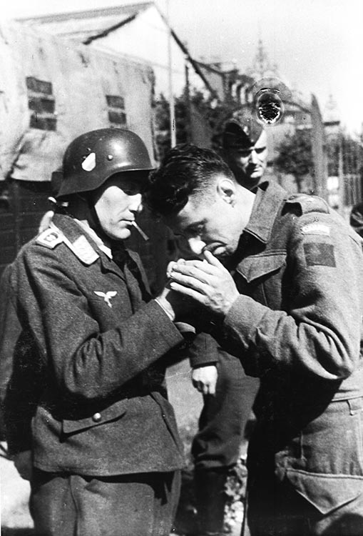 A German soldier interacts with Canadian prisoners of war following the Dieppe Raid, which took place on August 19, 1942. It was not a success for the Allies, though Honorary Colonel David Lloyd Hart, the Canadian Army's longest-serving officer, was awarded the Military Medal for his actions.