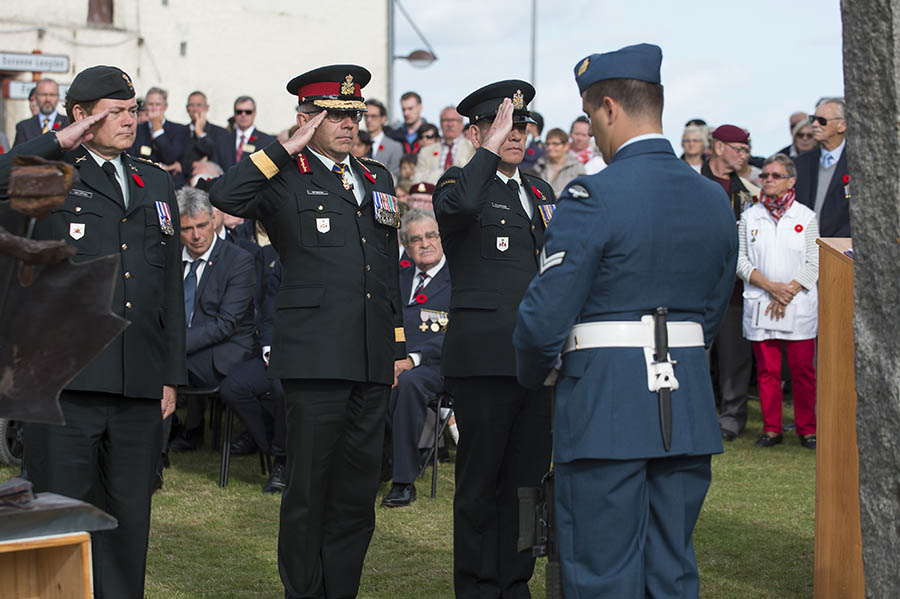 Honorary Colonel Blake Goldring, Honorary Colonel of the Canadian Army (left), Lieutenant-General Paul Wynnyk, Commander of the Canadian Army (centre), and Chief Warrant Officer Alain Guimond, Sergeant Major of the Canadian Army (right) salute the Pourville monument during a ceremony commemorating the 75th anniversary of the Dieppe Raid on August 20, 2017.  