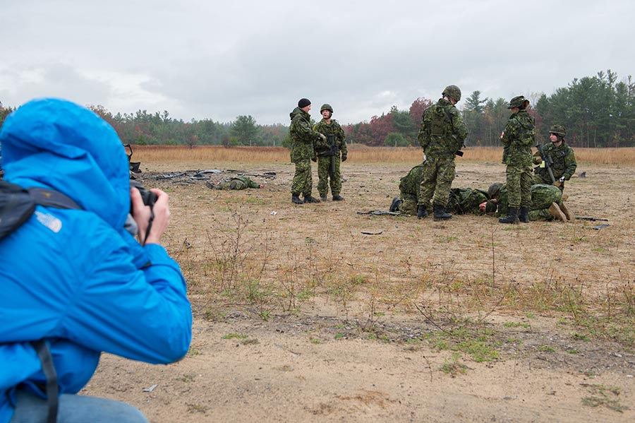 A Carleton University journalism student takes a picture of a simulated improvised explosive device scenario during Exercise ARDENT DEFENDER 2017 in Borden, Ontario, October 28, 2017. Photo: Corporal Joey Beaudin, 19 Wing Imaging. ©2017 DND/MDN Canada.
