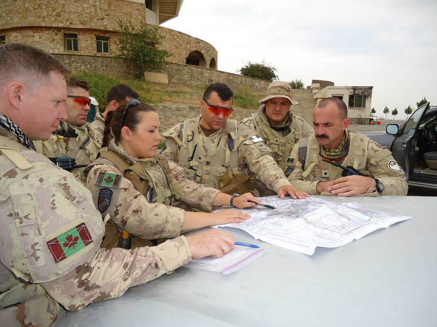 Captain Gillian Dulle (centre), in October 2011 in Kabul, Afghanistan. The group is part of the Operation ATTENTION Roto 0 who was mentoring the Afghan National Army at their staff college.