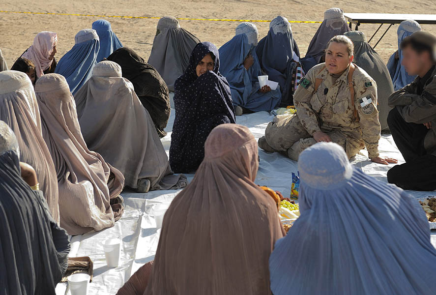 With the aid of an interpreter, Lieutenant Gillian Dulle, a volunteer from Camp Nathan Smith, speaks with some Afghan women on November 21, 2009 as they share some refreshments during the celebration of Eid al-Adha organized by the Kandahar Provincial Reconstruction Team. Eid al-Adha is a Muslim Holiday celebrated by Muslims worldwide. 