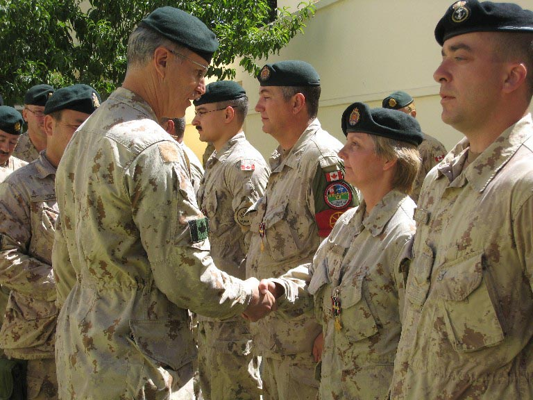 Sergeant Cheryl Crispin shaking hands with Major-General Tim Grant, Commander, Joint Task Force Afghanistan, as she receives the General Campaign Star - South West Asia Medal for her work in Afghanistan in 2007. 