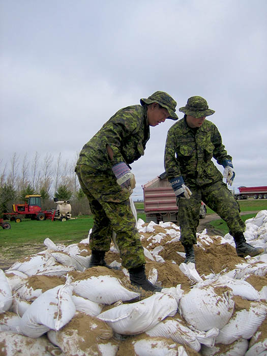 In 2011, Sergeant John Ta, pictured left, deployed to Manitoba for two months as part of Operation LUSTRE, the Canadian Forces flood-mitigation operation. One of the highlights of his career, Sgt Ta enjoyed the fact he was able to help fellow Canadian citizens in their time of need. Photo: provided by Sergeant John Ta.