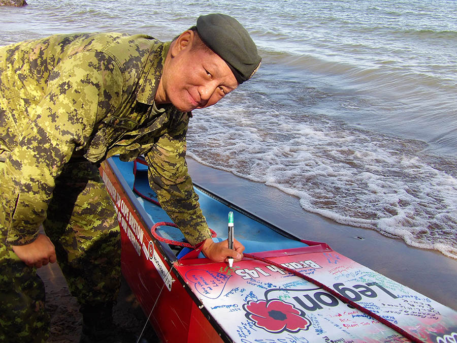 Sergeant John Ta signs the canoe of Mike Ranta during Mr. Ranta's brief stop in Thunder Bay during his cross-Canada canoe paddle and portage in support of Canadian Armed Forces veterans during the summer of 2016. Photo: provided by Sergeant John Ta.