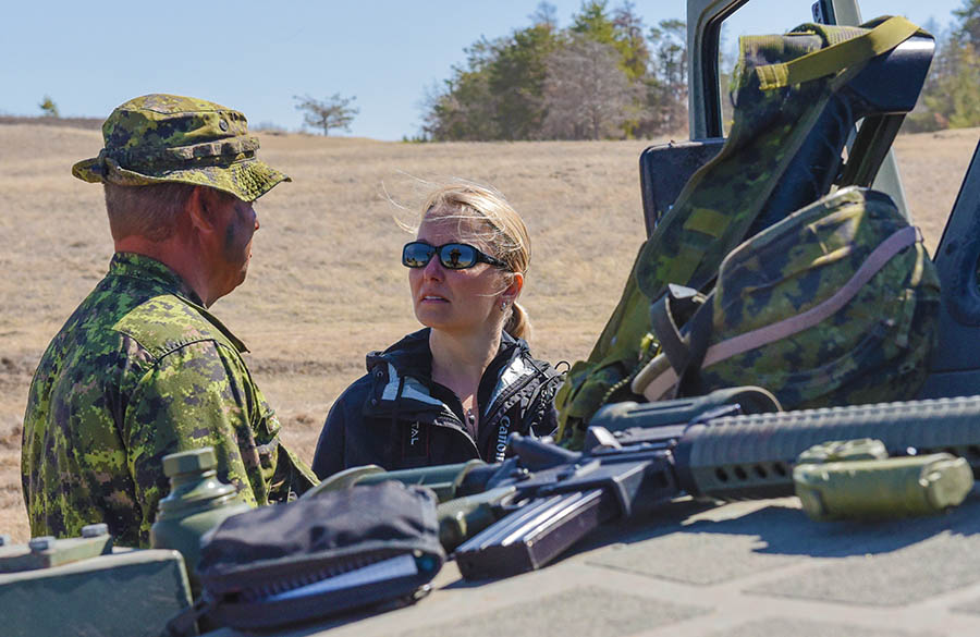 Sergeant Taylor Warren of The Fort Garry Horse gives his civilian employer, Julie Baines, of the Canada Border Services Agency a quick explanation of the equipment he uses out in the field. Ms. Baines came out to Exercise ARMOURED BISON 2018 as part of the Canadian Forces Liaison Council ExecuTrek, a program designed to show civilian employers how their Army Reservist employees train for military service.