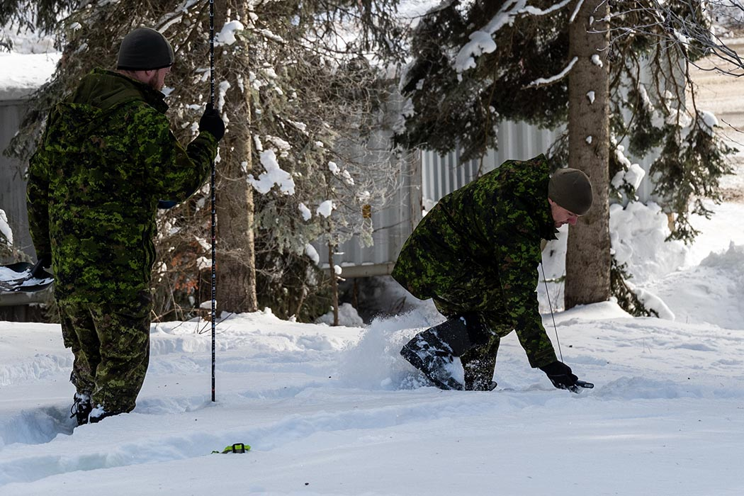 Sergeant Francis Benoit and Sergeant Jason Debourke demonstrating basic avalanche search and rescue.