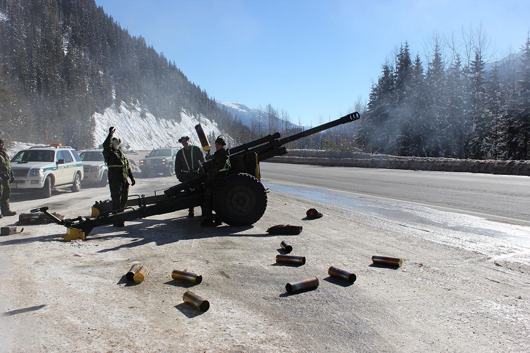 Members of 5e Régiment d'artillerie légère du Canada discard expended shells on the side of the Trans-Canada Highway in Rogers Pass, British Columbia on February 26, 2014. The ongoing relationship since 1961 between Parks Canada and the Canadian Armed Forces during Operation PALACI ensures the safety of Canadians travelling in high risk avalanche areas along the Trans-Canada Highway. Photo: Parks Canada.