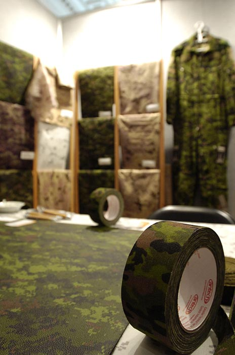 Various military textiles and personal equipment on display at a trade show. A procurement project launched in February 2019 is considering replacements for the Arid Region and Temperate Woodland versions of the Canadian Armed Forces' Canadian Disruptive Pattern (CADPAT) uniform, which have been in service for over 20 years. Photo: Sergeant Robert Comeau, Army News. ©2008 DND/MDN Canada.