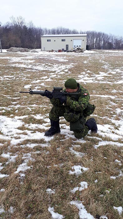 Soldier kneels down aiming rifle