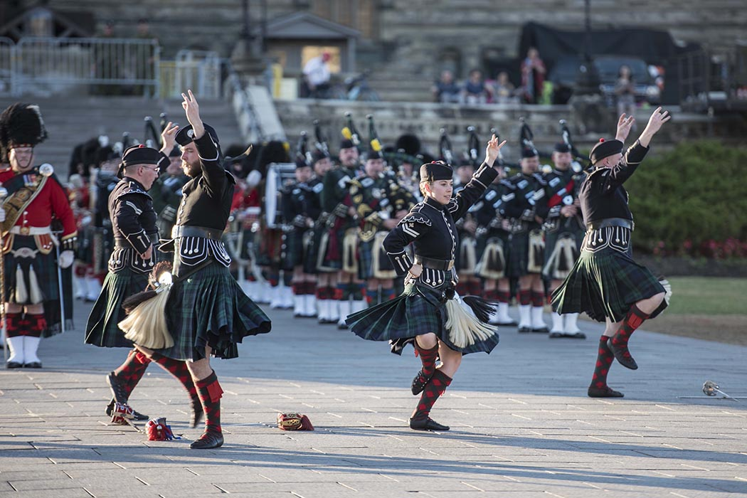Members of the massed Pipes and Drums of the Canadian Armed Forces dance in front of Parliament Hill as part of the annual Fortissimo military sunset ceremony in Ottawa, Ontario in July 2018. Photo: Ordinary Seaman Camden Scott, Army Public Affairs. ©2018 DND/MDN Canada.