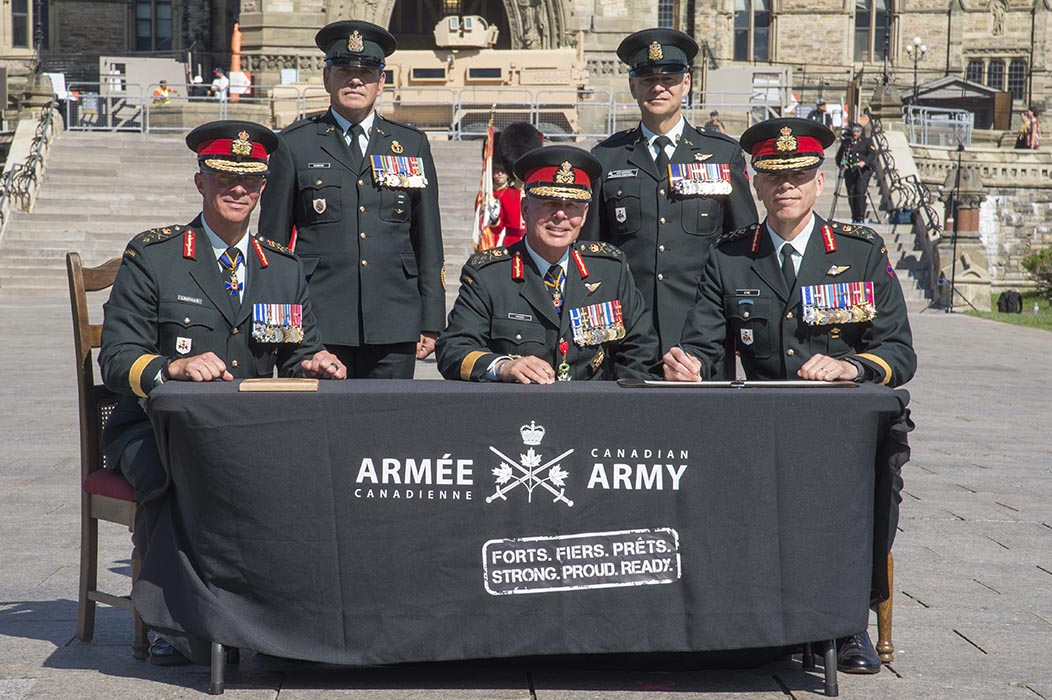 General Jonathan Vance, Chief of the Defence Staff, (centre) Lieutenant-General Jean-Marc Lanthier, outgoing Commander of the Canadian Army, (left) and incoming Commander Lieutenant- General Wayne Eyre (right) sign the ceremonial Change of Army Command scrolls during the Canadian Army Change of Command ceremony at Parliament Hill in Ottawa, Ontario on August 20, 2019.  Also pictured are Chief Warrant Officer Alain Guimond, (second left) Canadian Armed Forces Chief Warrant Officer; and Chief Warrant Officer Stuart Hartnell, (second right) Canadian Army Sergeant Major. Photo: Sergeant Lance Wade, 5th Canadian Division. ©2019 DND/MDN Canada.