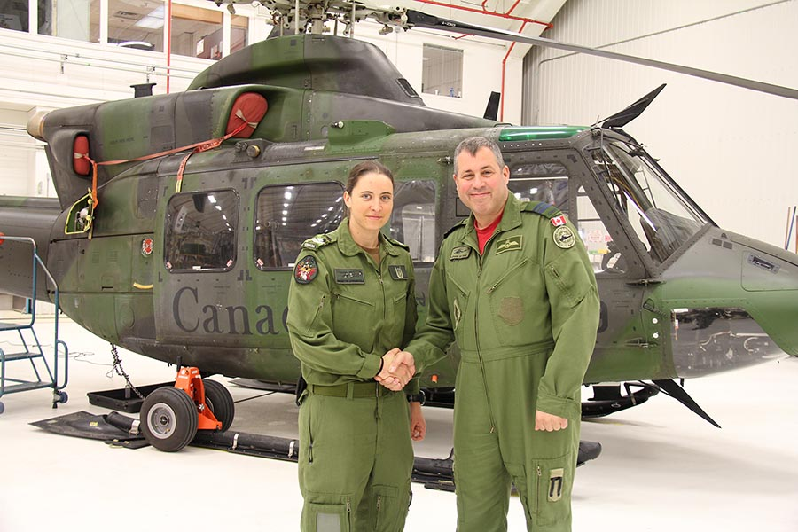 Major Stéphane St-Onge, 438 Tactical Helicopter Squadron acting commander, congratulates Master Corporal Brigitte O'Driscoll on the receipt of her Door Gunner badge on May 10, 2019. Photo: Corporal Laura Landry, 438 Tactical Helicopter Squadron. ©2019 DND/MDN Canada.