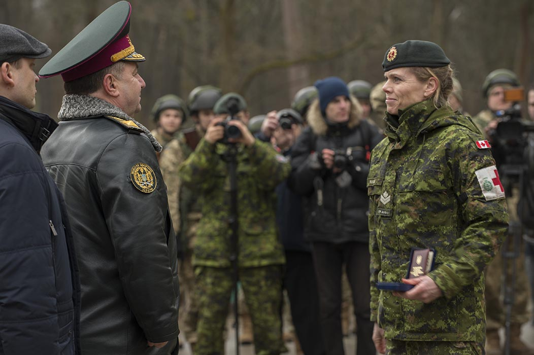 Master Corporal Jennyfer Russell receives a commendation from the hands of the Ukrainian Minister of Defence, General Stepan Poltorak, during Operation UNIFIER at the International Peacekeeping and Security Centre in Starychi, Ukraine on March 15, 2016.  Photo: Canadian Forces Combat Camera. ©2016 DND/MDN Canada. IS03-2016-0017-008.