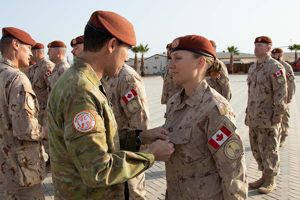 Major General Simon Stuart, Multinational Force and Observers (MFO) Commander, presents the MFO Medal to Corporal Currie during a medals ceremony marking the end of Canada's four-year commitment of Military Police to the MFO on March 20, 2019 at MFO South Camp in Sharm El Sheikh, Egypt.  Photo: Sergeant Vincent Carbonneau, Canadian Forces Combat Camera. ©2019 DND/MDN Canada. S02-2019-0001-026.