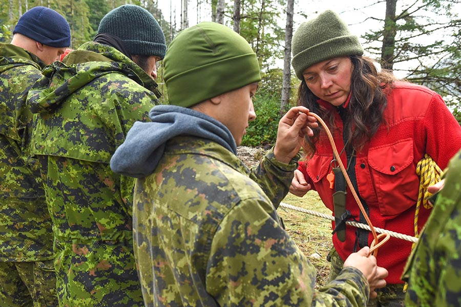 Canadian Ranger Sergeant Emily Coombs, Patrol Commander for the Ucluelet Canadian Ranger Patrol, teaches soldiers from 3rd Canadian Division how to properly tie knots during the Enhanced Wilderness Survival Training course on September 27, 2019 in Coal Harbour on the North coast of Vancouver Island. Photo: 4th Canadian Ranger Patrol Group. ©2019 DND/MDN Canada.