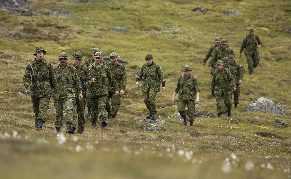 Soldiers from 2nd Battalion, The Royal Canadian Regiment (2RCR), return from a tasking during Exercise NARWHAL, which took place August 13-24, 2004 in the Cumberland Peninsula area of Baffin Island.  The troops are wearing CADPAT (Canadian Disruptive Pattern) uniforms which provide effective camouflage in this environment. Photo:  Sergeant Frank Hudec, Canadian Forces Combat Camera. ©2004 DND/MDN Canada.