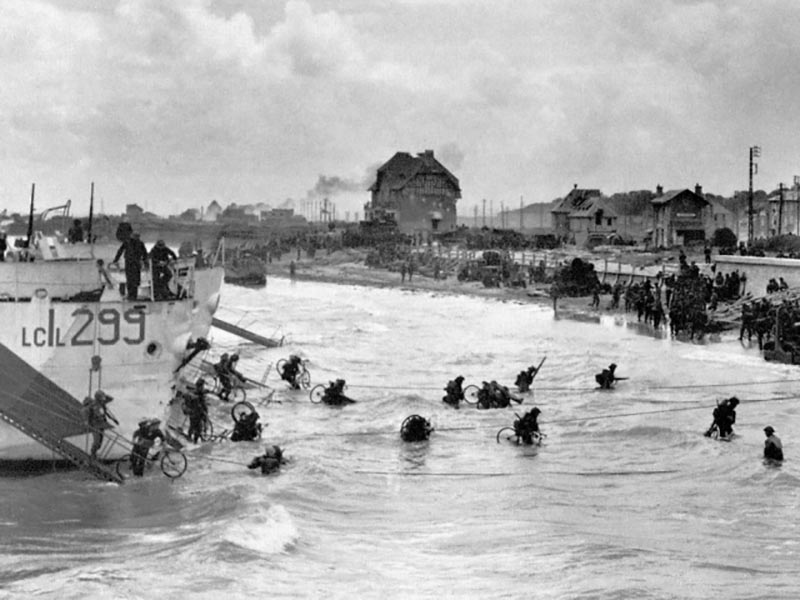 On D-Day, soldiers of the Stormont Dundas Glengarry Highlanders arrive on the white beach of the town of Berniers Sur Mer, France. They had trained for years in England. Photo provided by Canadian Research and Mapping Association (CRMA)