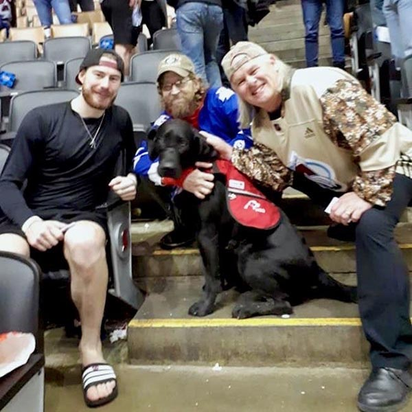 "Leafs fan Sgt (Retd) Kevin Barter, Thunder, friend Neil Washer and Colorado Avalanche goalie, Philipp Grubauer, December 4, 2019, Scotiabank Arena, Toronto. ""They gave us special seats and brought out a dish of water for Thunder. He didn't like when the music got loud, so that's when they let me take him out for a pee."" Photo provided by Sgt (Retd) Kevin Barter"