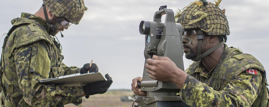 Slide - Soldier looking through the GLPS theodolite while the other looks at the clipboard