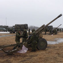 Soldiers loading a C3 Howitzer.