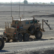A Buffalo vehicle uses its extendable arm to investigate a possible mine or improvised explosive device.